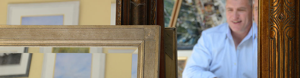 Keith Wilkinson picture framer seen in mirror with frames