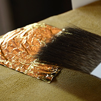Brushing gold leaf